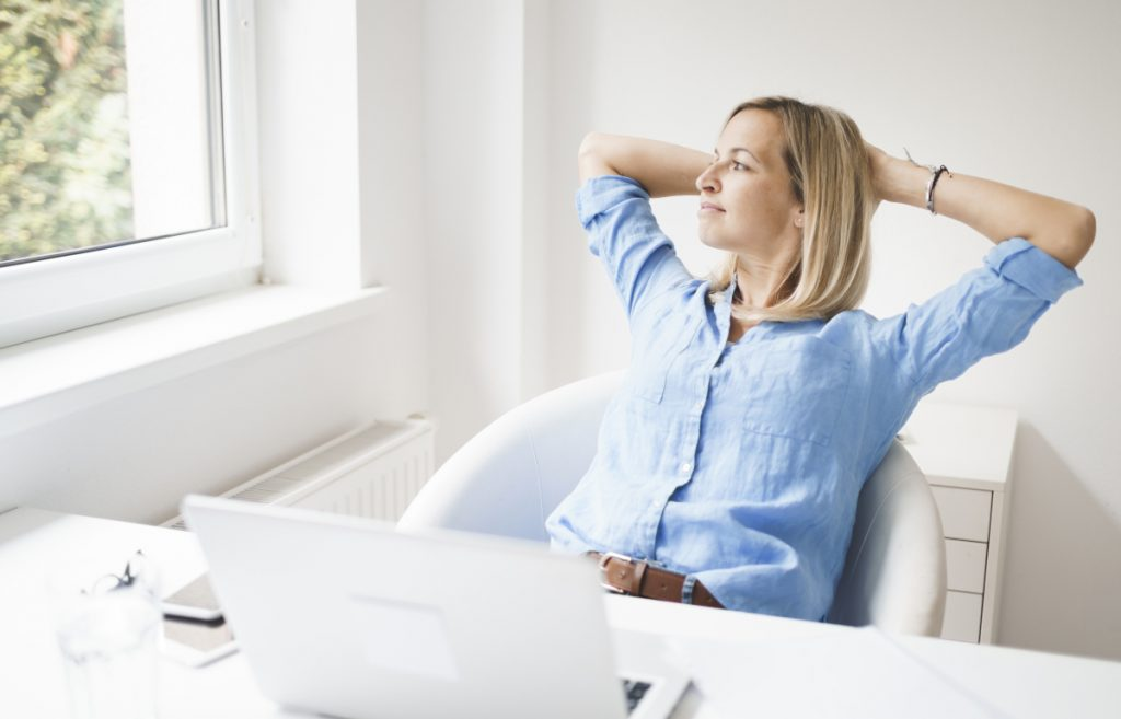 Business woman relaxing at her desk - photo by epixproductions from AdobeStock